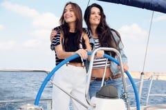 有放松在游艇的黑发的美丽的妇女在公海 库存图片