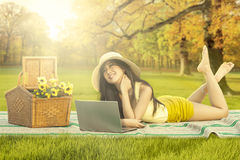 有放松在秋天公园的膝上型计算机的愉快的妇女 库存照片