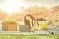 有放松在秋天公园的膝上型计算机的美丽的女孩 免版税库存图片