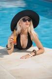 有放松在水池的时兴的太阳镜的美丽的肉欲的金发碧眼的女人用汁液 黑色的可爱的长的头发妇女 库存图片