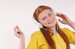 有放松由听的音乐的耳机的美丽的年轻红色头发女孩 免版税图库摄影