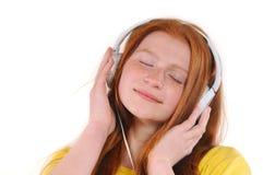 有放松由听的音乐的耳机的美丽的年轻红色头发女孩 库存图片