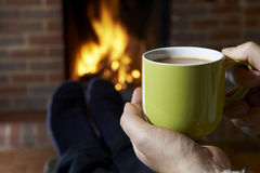 有放松由火的热的饮料的人 免版税库存图片