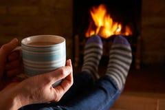 有放松由火的热的饮料的妇女 免版税图库摄影