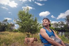 有放松的Shar裴狗的年轻人享受在河岸的自然 免版税库存图片