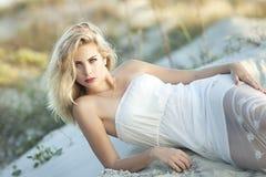 有放置在与一件白色鞋带礼服的沙子的蓝眼睛的一名美丽的白肤金发的妇女  免版税库存图片
