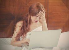 有放置在卧室床上的膝上型计算机的画象哀伤的不快乐的妇女  图库摄影
