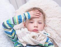 有放置在床上的温度计的哀伤的病的男孩 免版税图库摄影