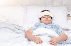 有放置在床上的温度计的病的男孩 免版税图库摄影