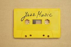 有放置在纸背景的爵士音乐的减速火箭的黄色卡型盒式录音机磁带 免版税库存照片