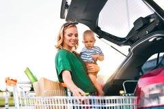有放购物的男婴的母亲入汽车后面  库存图片