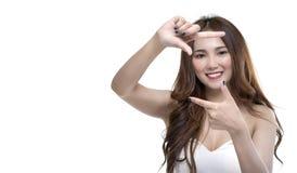 有效地做框架圆的姿态的愉快的正面年轻亚裔女孩画象在照相机 库存照片
