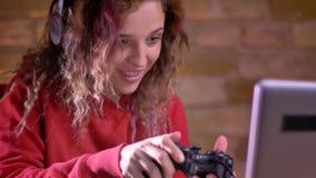 有效地打电子游戏的年轻女性博客作者特写镜头画象使用控制杆bricken墙壁背景 股票录像