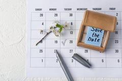 有救球的箱子日期卡片、标志和开花的分支在日历 库存照片