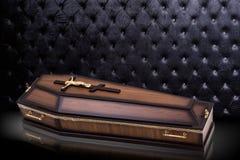 有教会十字架的闭合的木棕色棺材在灰色豪华背景 在皇家背景的小箱 免版税库存图片