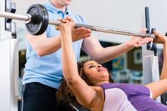 有教练员举的重量的黑人妇女在健身的健身房 免版税库存照片