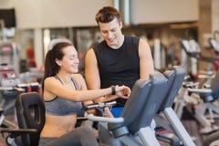 有教练员的愉快的妇女在健身房的锻炼脚踏车 库存照片