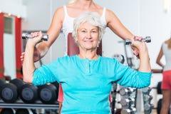 有教练员的资深妇女在健身房举的哑铃 免版税库存照片