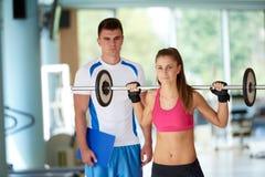 有教练员锻炼举重的年轻运动的妇女 免版税库存照片