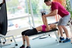 有教练员锻炼举重的年轻运动的妇女 库存图片