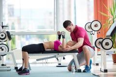 有教练员锻炼举重的年轻运动的妇女 免版税图库摄影