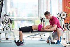 有教练员锻炼举重的年轻运动的妇女 免版税库存图片