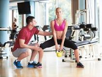 有教练员锻炼举重的年轻运动的妇女 图库摄影
