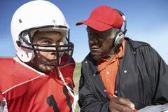 有教练的橄榄球球员 免版税库存图片