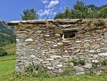 有散石墙壁和窗口的遗弃谷仓在奥地利阿尔卑斯 免版税库存照片