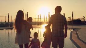 有敬佩日落的三个孩子的愉快的家庭在水池的表面反射了 免版税库存图片