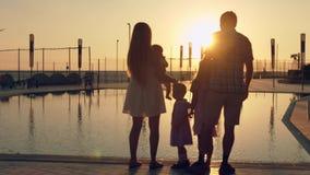 有敬佩日落的三个孩子的愉快的家庭在水池的表面反射了 库存照片