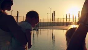 有敬佩日落的三个孩子的愉快的家庭在水池的表面反射了 免版税库存照片