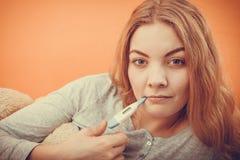 有数字体温计的病的不适的妇女在嘴 免版税库存图片
