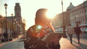 有数字式垫的年轻性感的可爱的女孩浏览在城市街道上的互联网在早晨阳光日出 影视素材
