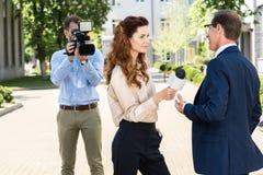 有数字式摄象机的专业摄影师和新闻记者采访的商人 免版税库存照片
