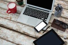 有数字式桌、手机和咖啡的膝上型计算机 免版税图库摄影