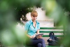 有数字式片剂个人计算机的西班牙妇女在长凳 免版税库存照片