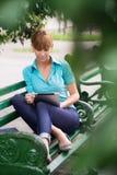 有数字式片剂个人计算机的西班牙妇女在长凳 图库摄影