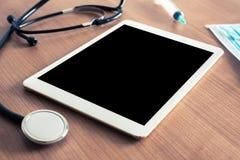 有数字式片剂和听诊器的医疗书桌 消息的空白 图库摄影