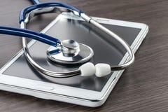 有数字式片剂和听诊器的医生工作场所 免版税库存图片