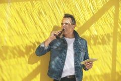 有数字式片剂和啤酒的老人在黄色墙壁上。 免版税库存图片