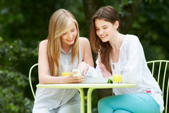 有数字式片剂和手机的十几岁的女孩在咖啡馆 免版税库存图片