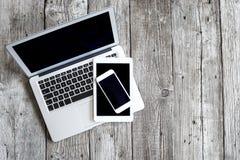 有数字式片剂和手机的膝上型计算机在木桌上 库存图片