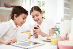 有数字式片剂和机动性的学童在早餐 库存照片