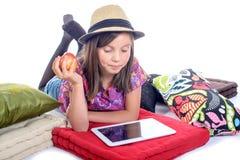 有数字式片剂和果子的女小学生 图库摄影