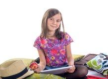 有数字式片剂和果子的女小学生 免版税图库摄影