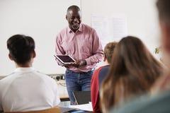 有数字式片剂教的类的男性学院家庭教师 免版税库存图片