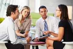 有数字式片剂的买卖人开会议在办公室 免版税库存图片