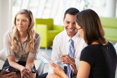 有数字式片剂的买卖人开会议在办公室 库存图片