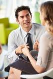 有数字式片剂的买卖人开会议在办公室 库存照片
